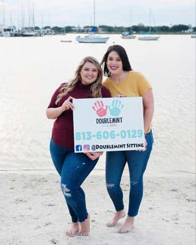 2 young ladies holding a sign on the beach